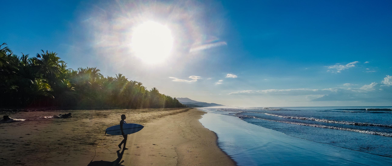 Silene Vega Walking to Beach with surfboard